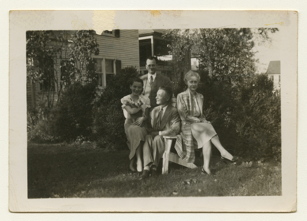 A black and white outdoor family photo of Anne Wilson, three of her family members, and a cat.