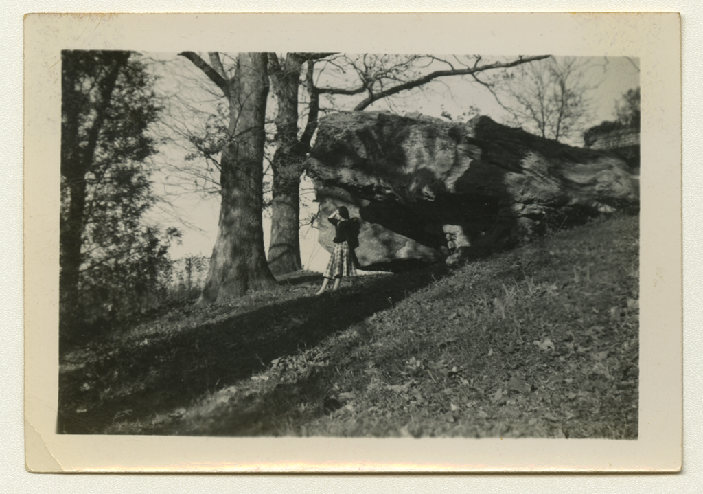 A black and white long-shot photograph of Anne Martin Wilson posing under a large rock in a grassy area