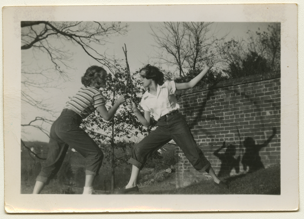 """A black and white photo of a young Alma and Anne Rowe """"sword fighting"""" with sticks next to a brick wall"""