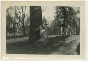 Black and white polaroid of Sandra Maynard crouched by a tree