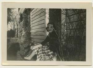 Black and white polaroid of Anne Wilson wearing a jacket and dress sitting on a porch