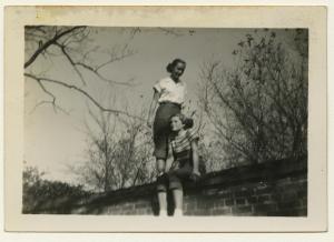 Black and white polaroid of Sandra Maynard and Alma Rowe atop a brick wall